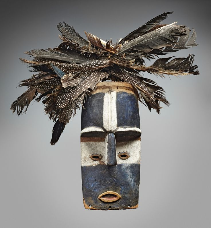 AN ADUMA MASK  Gabon  The rectangular face with prominent forehead, pierced eyes flanking the rectangular nose, painted blue, white, red and reddish brown, feather crest.  32 cm. high