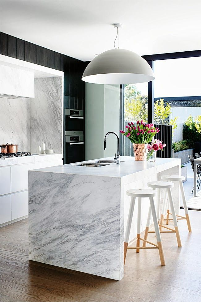marble waterfall countertop on this kitchen island--image via Amy Benton