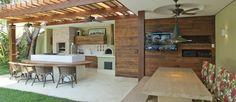 A cozinha gourmet, dos arquitetos Bruno Carvalho e Camila Avelar, tem chopeira, chapa e churrasqueira. Na parte coberta, área para assistir à TV e comer Foto: Divulgação