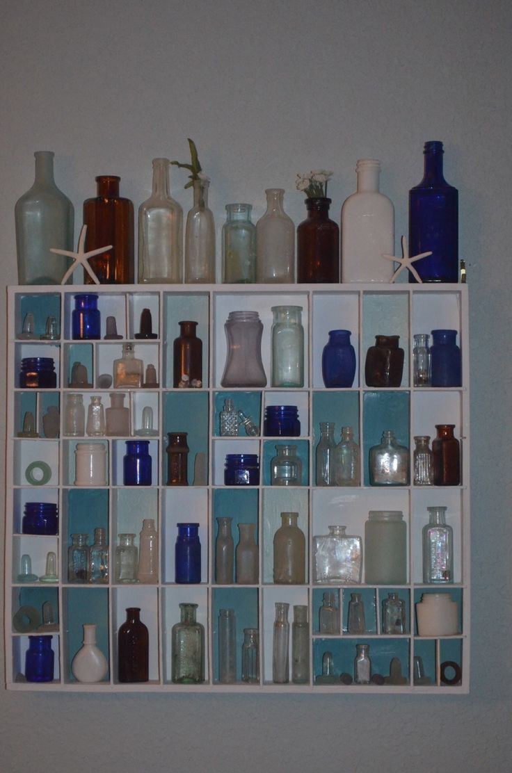 sea glass shadow box, beach shadow box $5 junkyard find, rebuilt shelves, a few coats of paint and now my most prized sea glass bottles and stoppers have a respectable home:)