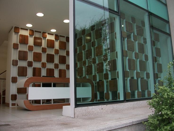 Mesa de recepción enchapada, con tubos de acero inoxidable a medida.  Frentes enchapados con madera natural.  Panel divisor, en fierro esmaltado con placas de madera natural.