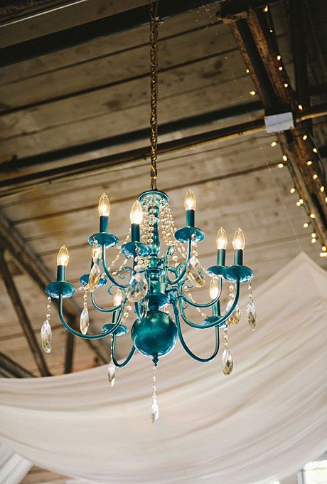 """Brides.com: . """"My absolute favorite?"""" Christina says. """"Two funky, ocean blue chandeliers were hung overhead just below the swags on each side of the room. Love, love, loved these."""""""