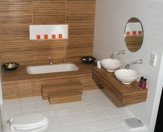 1:12 bathroom in zebrano wood    1:12 dollhouse bathroom with recessed shelf with 12v tealights set into wall clad in real zebrano wood. Sunken tub set in a dais with steps leading to it. Double vanity unit with round china bowls.