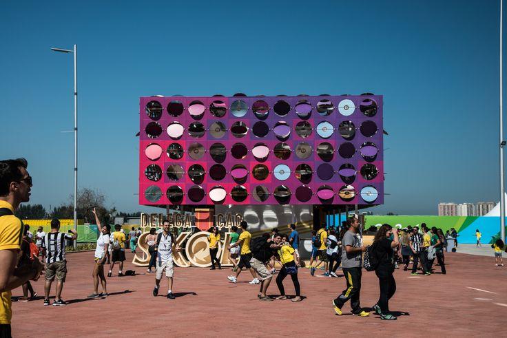 """Desenvolvido para as Olimpíadas Rio 2016, o Pavilhão Dançante é """"uma arquitetura interativa temporária criada para o Parque Olímpico. Sensores dispersos por uma pista de dança captam a batida da música e o movimento das pessoas, ativando os motores dos espelhos na fachada do prédio. O resultado é uma arquitetura cinética que hipnotiza as pessoas e transforma o espaço no clube de dança mais emocionante das Olimpíadas de 2016"""", explica a página oficial do CODAawards 2017."""