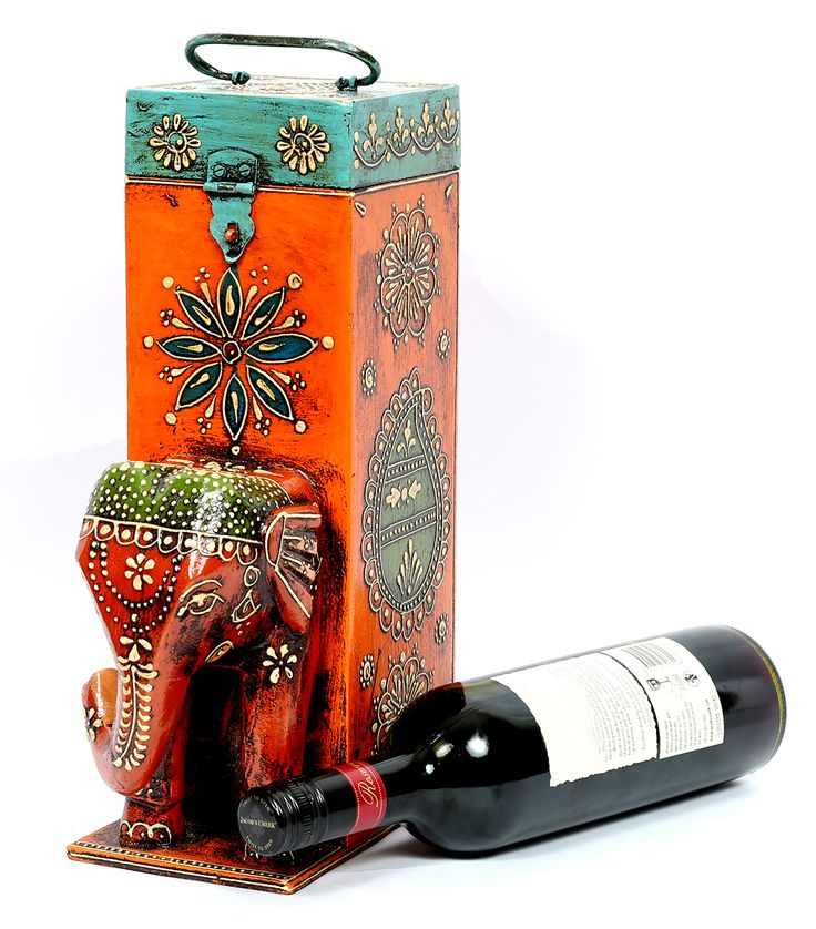 """Wine bottle holder. Handcrafted with inticate design and adorned with an elephant head. Exquisite. Ethnic. Classy. Will add the 'WOW"""" factor into your decor.  Get the best for your fine wine. This artistic and ethnic wine bottle holder is crafted in white wood. This wine holder is accented with a royal elephant that has been embossed hand painted in shades of red and black with delicate designs in white for an alluring look. The Rajasthani hand is evident in the flawless work done on the…"""