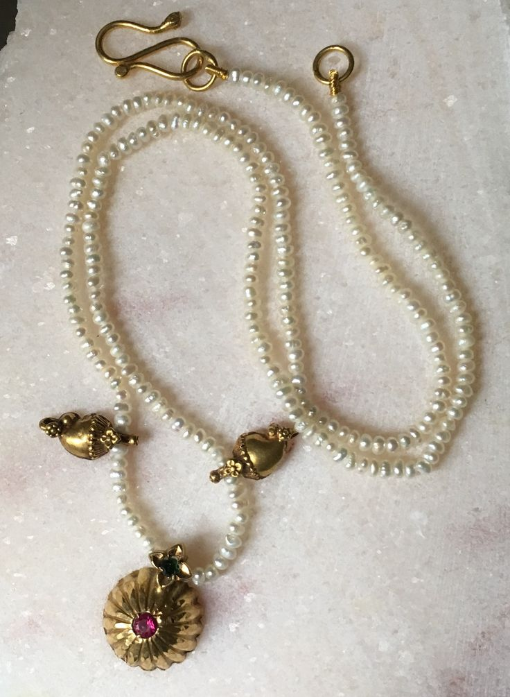 Necklace of tiny pearls and Indian old gold charms.