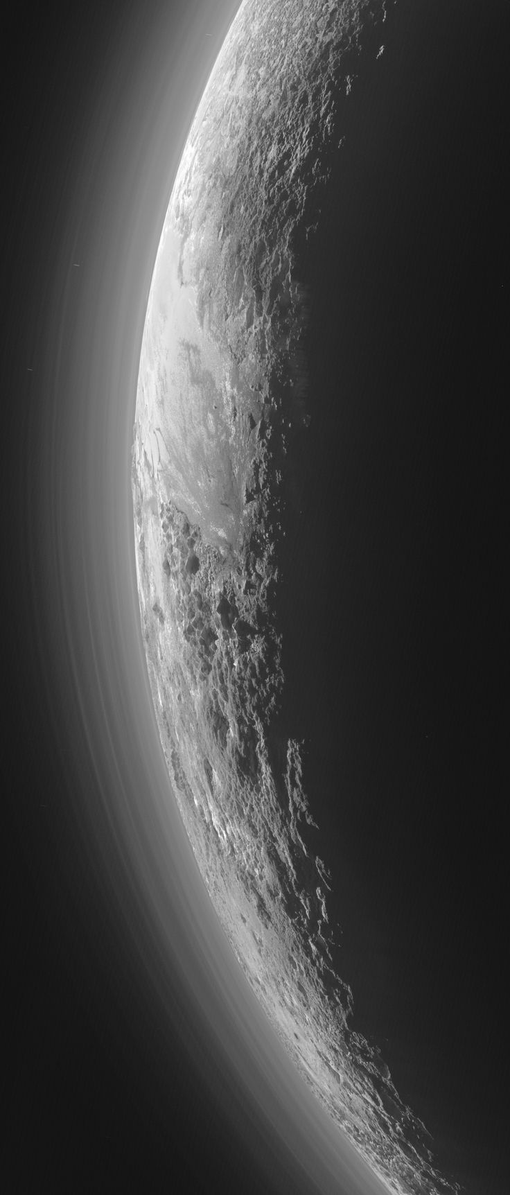 Only 15 minutes after its closest approach to Pluto on July 14, 2015, NASA's New Horizons spacecraft looked back toward the sun and captured this near-sunset view of the rugged, icy mountains and flat ice plains extending to Pluto's horizon. The smooth expanse of the informally named icy plain Sputnik Planum (right) is flanked on the left by rugged mountains up to 11,000 feet (3,500 meters) high, including the informally named Norgay Montes in the foreground and Hillary Montes on the…