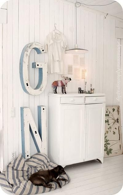 Witte houten hal met grote vintage letters aan de muur en gezellig slaapkussen voor de hond.