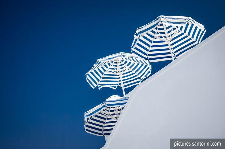 Sun umbrellas striped in blue and white against a deep blue sky.