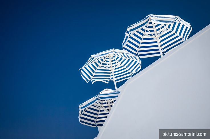 Sun umbrellas striped in blue and white against a deep blue sky.