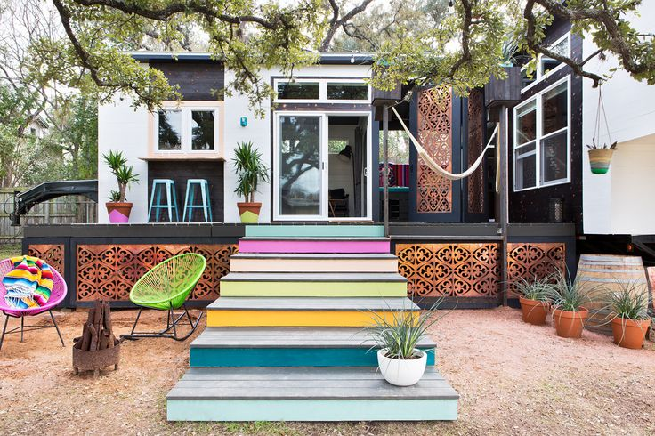 """You know me, I love color,"" confesses Lewis. ""But generally, I would say that when it comes to tiny homes, you want to minimize color on the inside. You can have more fun on the outside."" Here she does just that, with a set of extra-wide stairs in eye-catching shades and a weather-resistant rocker."