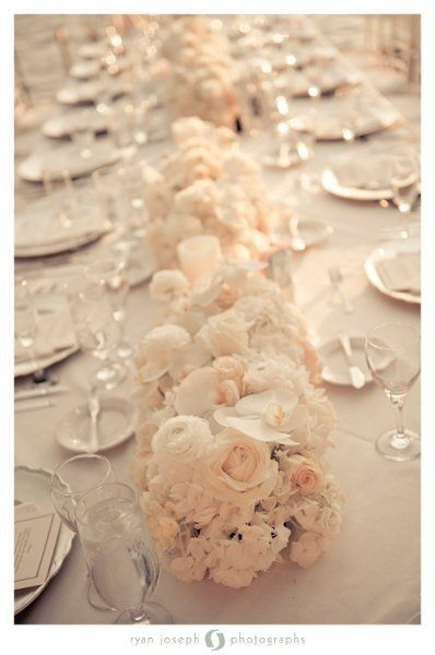 I like the simple flowers as a table runner. Would just have the candles in glass vases and add some variation in height. Flowers may be too cream/blush for me.