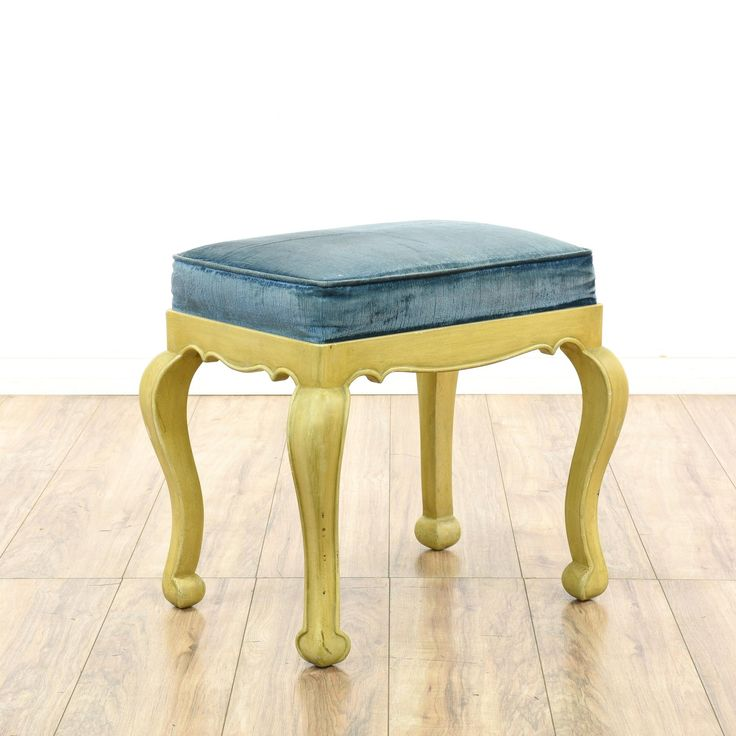 This ottoman stool is featured in a solid wood with a glossy yellow beige wood finish. This small bench has curved legs, carved trim and a blue corduroy upholstered seat cushion. Adorable stool perfect for a vanity or desk! #european #chairs #ottoman #sandiegovintage #vintagefurniture