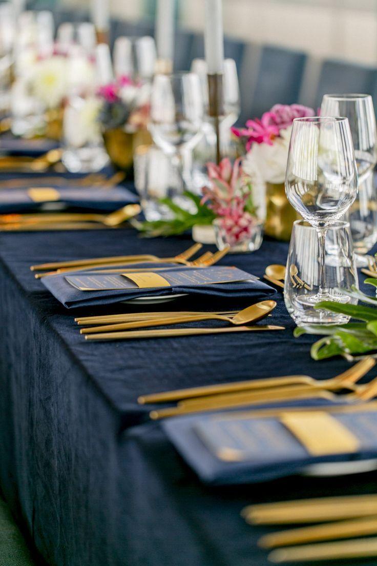 Gedeckter Tisch mit dunkelblauer Tischdecke und goldenem