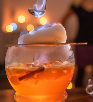 Weiße Feuerzangenbowle mit Äpfeln.  Zutaten für 6 Personen  2 Flaschen Weißwein (z. B. Chardonnay) 500 ml Apfelsaft 2 Äpfel 1 Zitrone 1 Orange 1,5 Zimtstangen 4 Nelken 2 – 3 Sternanis 1 Zuckerhut ca. 250 ml Weißer Rum (z. B. Arrak oder Wray & Nephew White Overproof)