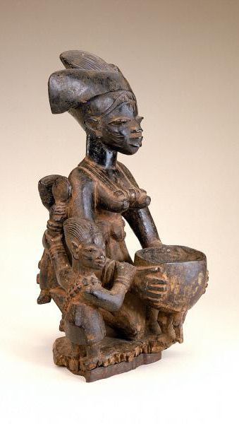 Africa | Female figure with children from the Yoruba people of Nigeria | Early to mid 20th century | Wood and pigment || Yoruba figurative sculptures for shrines dedicated to various deities often depict female devotees accompanied by children and holding bowls for kola nuts or other offerings.