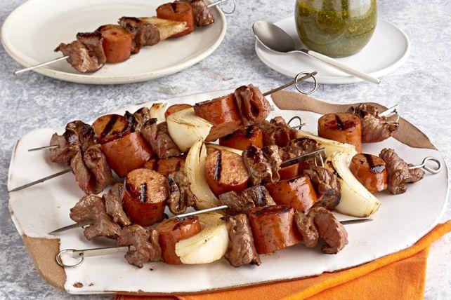 Le chimichurri est une sauce épaisse aux fines herbes qui accompagne généralement de la viande grillée. Ici, il complète des brochettes de bifteck, de saucisses de porc et d'oignon grillés.
