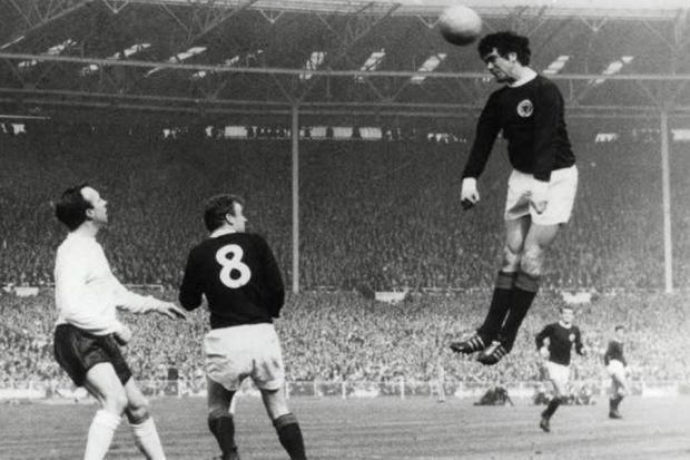 Jim Baxter gets in a header as team-mate Billy Bremner and England's Nobby Stiles look on during Scotland's 3-2 win at Wembley in 1967