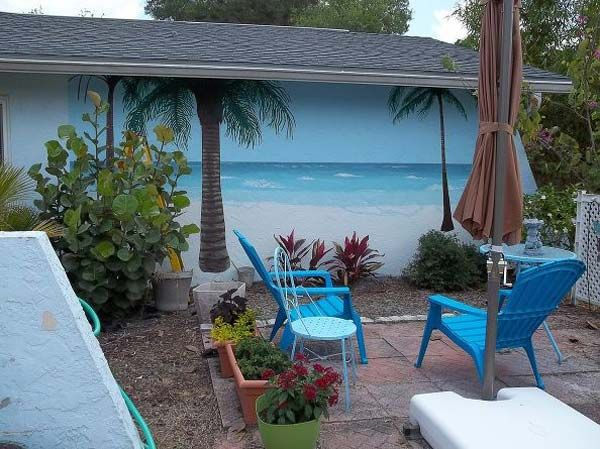 Seaside mural on a backyard wall: 27 Awesome Beach-Style Outdoor Living Ideas for Your Porch and Yard