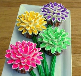 ❥ How to make Marshmallow Flower Cupcakes.  Cut mini marshmallows in half diagonally. Put in plastic bag with decorative sugars. Shake. Sugar only sticks to cut part. Let them sit and petals will puff up again. Attach with icing on cupcake.