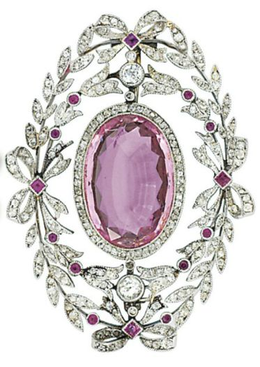 AN EARLY 20TH CENTURY PINK TOPAZ AND DIAMOND BROOCH. The oval-cut pink topaz to a millegrain-set old-cut diamond line surround, within a similarly-set laurel leaf and ribbon bow wreath frame, with further flowerhead and gem detail, circa 1905.
