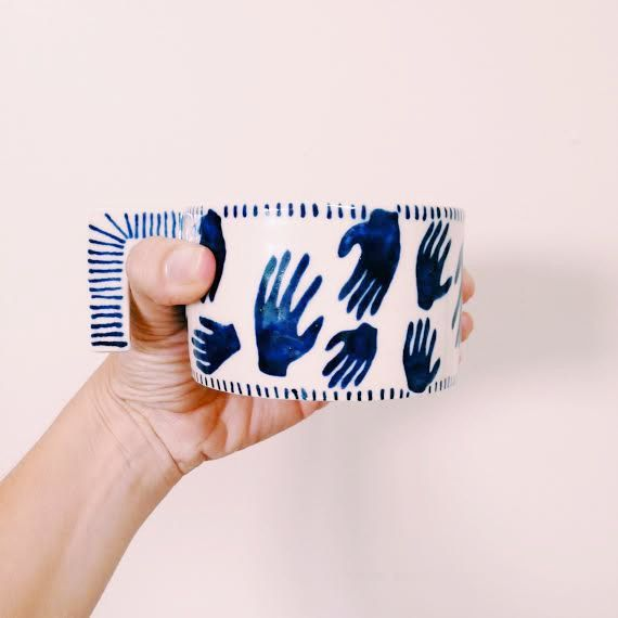 This cup has blue watercolour style hands and thin blue stripes.  The deep shade of the blue just makes this cup.