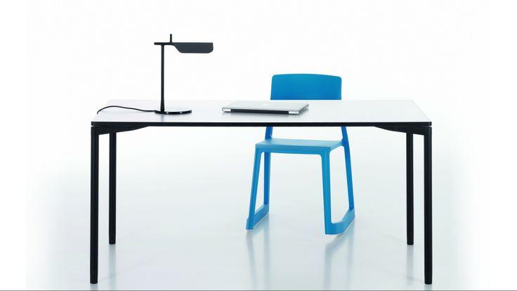 Smukłe biurko z niebieskim krzesłem.