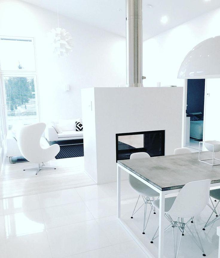 Valkoinen sitoo tilat yhteen. Särmää ja kontrastia kaiken keskelle tuo takan mustat yksityiskohdat ja taustalla näkyvä olohuoneen matto.