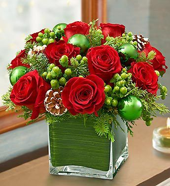 Melt their heart with a contemporary and cozy cube arrangement of fresh red roses, hypericum, Christmas greens and pinecone picks. Whether a...