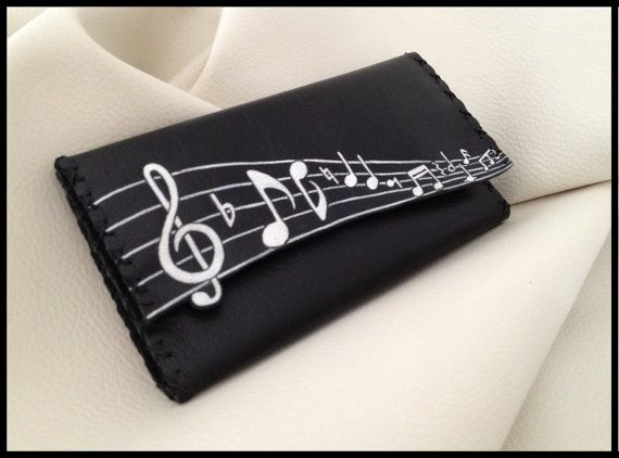 MUSICAL INSTRUMENTS..........!Tobacco pouch in genuine black leather ... The design is burnt with a pyrographer and painted with special colors for leather. Inside there are pockets for filters and papers, and closes with magnetic snaps.  Dimensions: 150mm x 200mm.