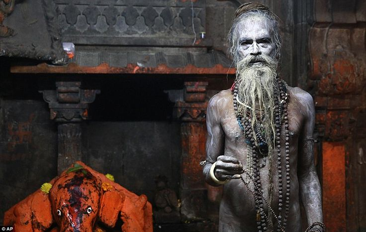 A Naga sadhu, or naked Hindu holy man, poses for a picture after taking a holy dip in the Godavari River during Kumbh Mela
