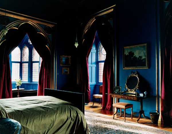 The royal blue walls and green bedspread are cool colors which create a calmness in the room while the red draperies create drama and excitement.