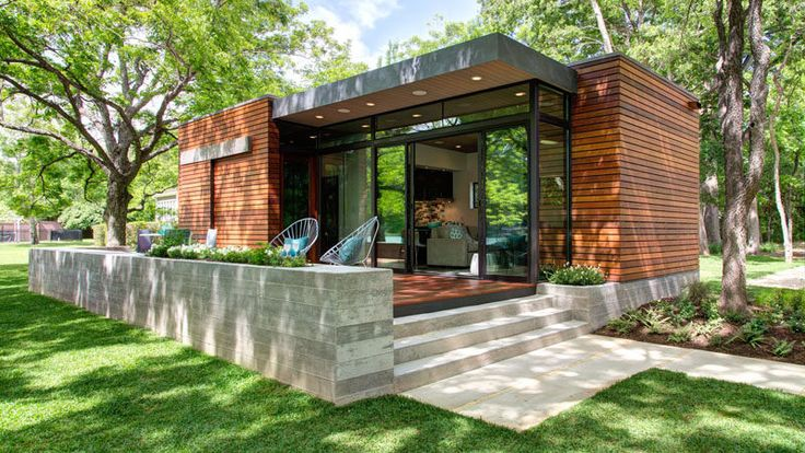 Ipe wood, steel, glass, and concrete was used to create this small modern lakeside cabin, that features a low board-formed concrete planter wall with herbs, a deck, a living/dining/kitchen area, a bathroom and a storage space.