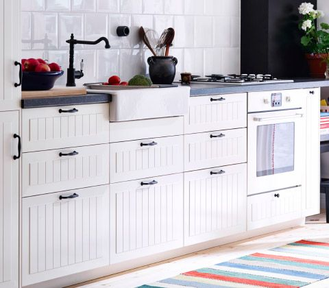 A view of the base cabinets and worktop of a ceam coloured, country-style kitchen with metal handles.