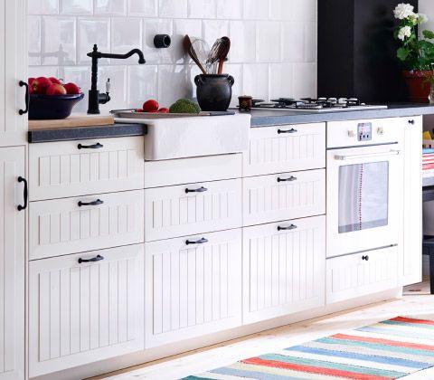 Zicht op de onderkasten en het werkblad van een crèmekleurige keuken in landelijke stijl met metalen handgrepen