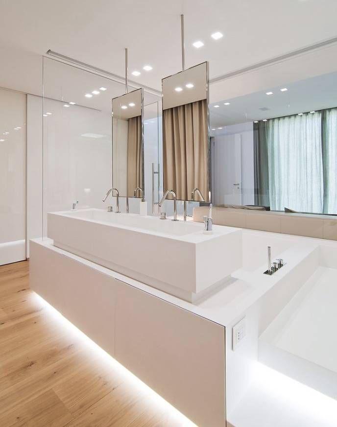 Bagno di design moderno con pareti bianche e pavimento in legno massello. La suddivisione dello spazio è realizzata con gli specchi sospesi. L'illuminazione artificiale gioca un ruolo fondamentale per creare l'atmosfera giusta per il massimo benessere e relax