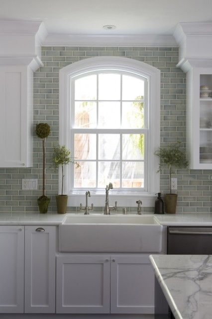 Like the arched window shape, how the soffit ends and cabinets frame the window, and the gray tile surrounding window.