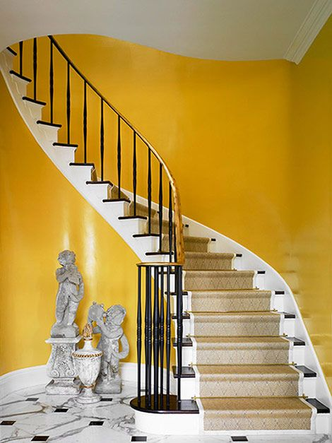The white stairs against the yellow walls show off the sculptural presence of the winding staircase. Design: Lee Bierly and Chris Drake. Photo: Robert Brantley
