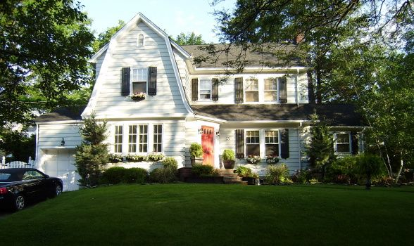 Dutch Colonial house exterior - white w/dark grey or black roof, black shutters and red front door