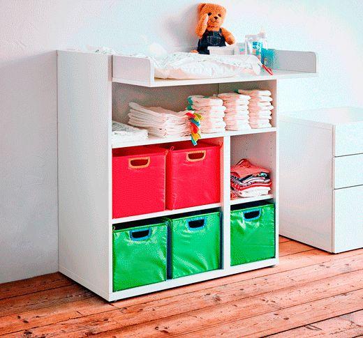 Table à langer placée contre un mur, contenant des bacs de rangement colorés et des couches