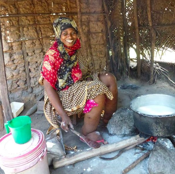 A beautiful woman smiling whilst washing dishes. Both her legs are grossly swollen from lymphatic filariasis
