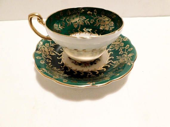 """The design is a green band with gold flowers and multifloral center display, gold accenting  The cup is 2 5/16"""" (5.9 cm) high x 3 11/16"""" (9.4 cm) at the brim and the saucer is 5 9/16"""" (14.1 cm) ) in diameter  This set is in very good condition and only appears to have seen use as a collectible  Made of bone china from England by Foley    These items have no nicks, chips, cracks, or signs of repair 