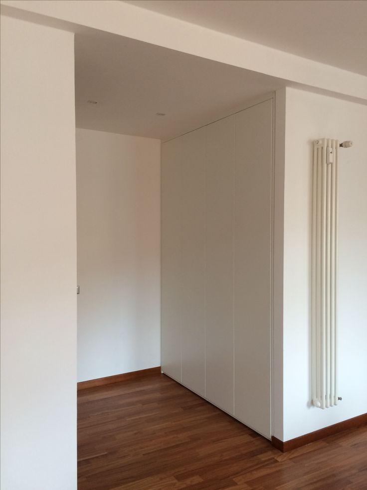 Un armadio a scomparsa, inserito tra le pareti e rifinito con coprifili dello stesso materiale e colore.
