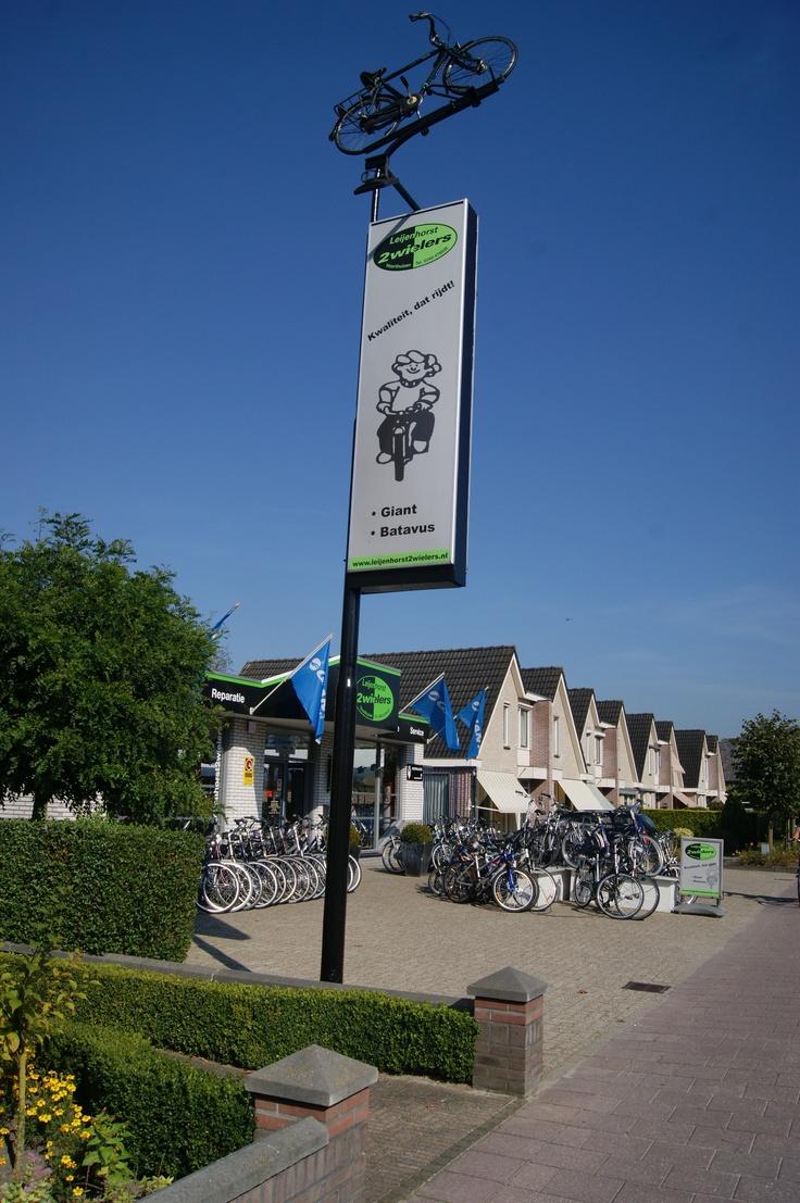 Ons kenmerk van onze winkel in Voorthuizen. Iedereen weet van de fiets bovenop de paal. En als het donker wordt geeft de fiets licht.