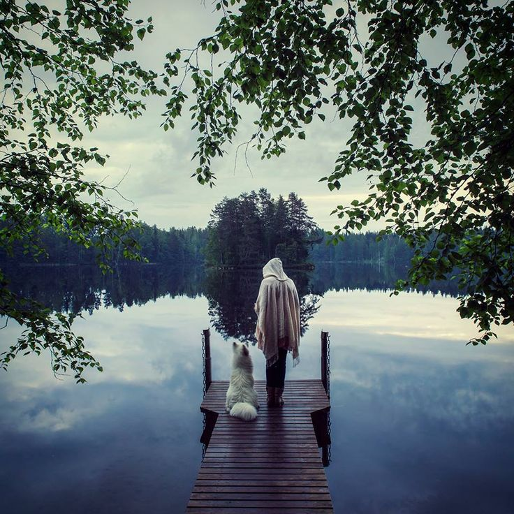 "Suvi Keiju: ""Me and my arctic samoyed dog standing by a silent lake on a midsummer night in Saimaa, Finland"". Photo by Sanna Kaitakari."