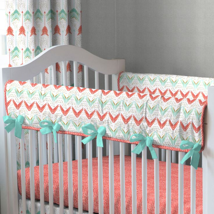 "Crib Rail Cover in Coral and Teal Arrow by Carousel Designs.  A perfect solution to help protect your baby's crib while maintaining a stylish decor for your nursery. Our Crib Rail Cover is reversible, enabling you to change the visible side at a moment's notice. Simply wrap the cover around your crib rail, pull the ties though the buttonhole and tie. The crib rail cover measures approximately 50"" long by 16"" wide. Please check your rail size to ensure proper fit."