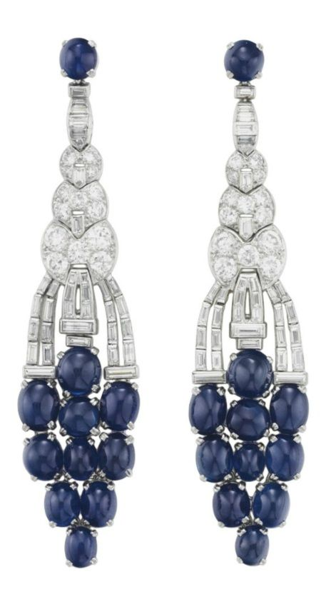 A PAIR OF ART DECO SAPPHIRE AND DIAMOND EAR PENDANTS, CIRCA 1925. Each designed as a flexible openwork baguette and circular-cut diamond plaque, suspending a tapered cluster of cabochon sapphires, 3 1/4 ins., with French assay marks for platinum. #ArtDeco #earrings