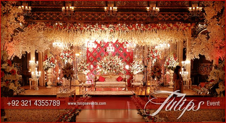 Red & Gold Pakistani wedding stage setup. hanging Crystal with various floral arrangements at backdrop. Amber gold lights ambience.  #themedweddings #red&gold #goldenweddings #tulipsevents #weddingsinPakistan #pakistaniweddings #pakistaniweddingideas