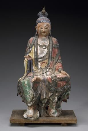 A fine polychromed stucco figure of Guanyin Ming Dynasty Seated in 'royal ease' with his right foot supported on a lotus leaf emerging from a faceted rock base attached to a wood-plank base, his elaborately arranged hair fronted by a miniature seated Buddha and his garments covered by a multi-pieced jiasha, all opening at the chest to reveal a princely necklace (chips, losses, repairs). Height 30in (76cm)