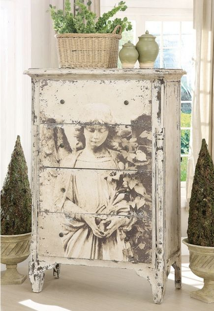 This looks like a decoupage of an image of an angle into the front of the dresser drawers... it looks amazing!
